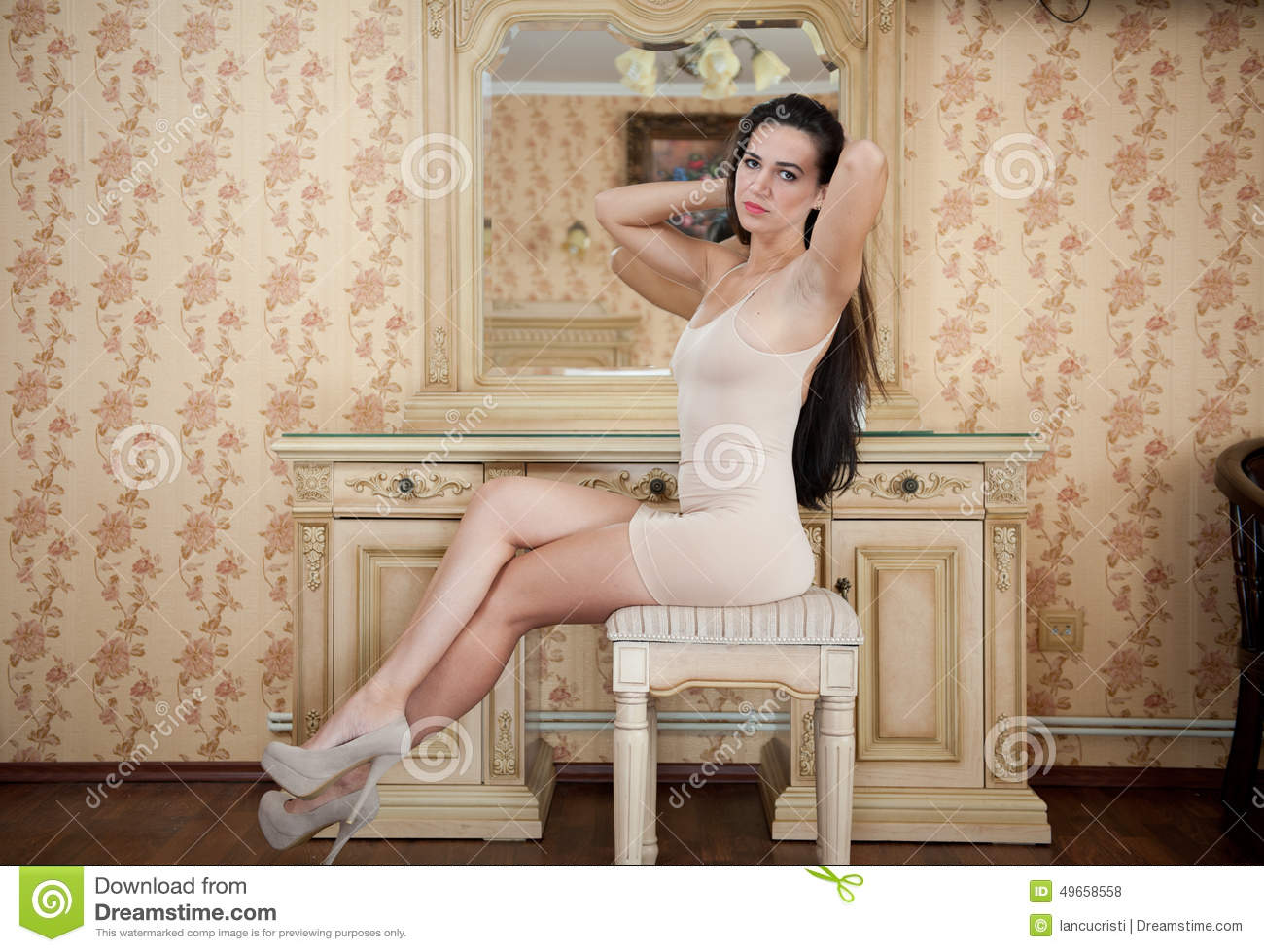 Young women sitting naked in front of mirror